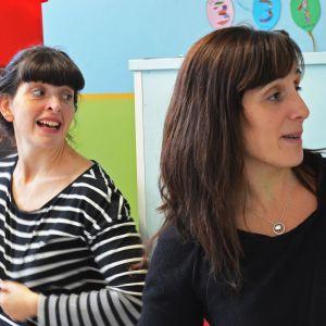 Två unga kvinnor i dagismiljö, skrattar.