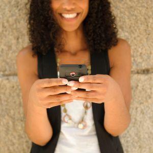 Tjej som tittar på en smarttelefon och skrattar.