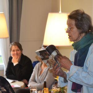 Poeten Sirkka Turkka läser en dikt. I bakgrunden syns några människor som lyssnar.
