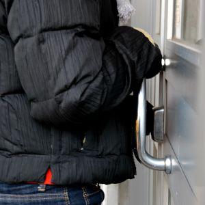 En person försöker bryta sig in genom en ytterdörr till ett höghus.
