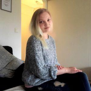 Johanna Karvonen, i sitt hem, sittandes på soffan.