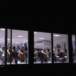 Danska roddare tränar på roddmaskiner, fotograferade genom fönster