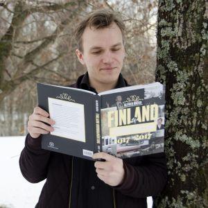 """Alfred Backa som står luta mot ett träd och läser sin bok """"Finland hundranånting""""."""
