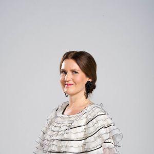 Pia-Maria Lehtola är klädd i en prickig vit festklänning.