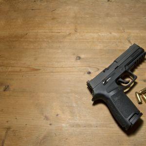 Bild på ett handeldvapen och kulor.