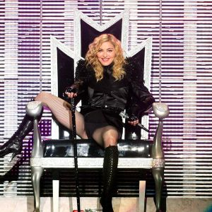 Madonna på scenen sitter i en stol med ena benet över ena armstödet.