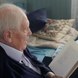 Lars Huldén sitter i en fåtölj och läser ur sina diktsamlingar