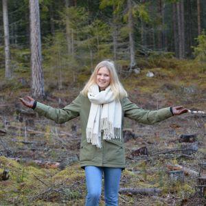 Flicka står ute i en skogsglänta.