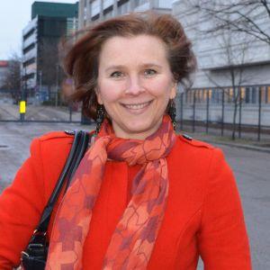 Pia Rinne ler i glatt röd kappa. Bakgrund gråtrist asfalt och betongbyggnad.