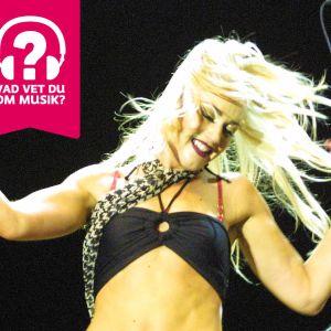 Gwen Stefani på scenen, leende och med fladdrande hår.
