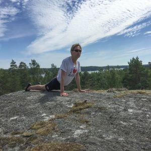 Kaj Arnö yogar på ett berg i skärgården
