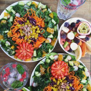 tallrikar fullastade med grönsaker och fruktbitar