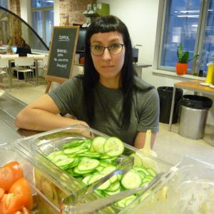 Freja Högback i en studierestaurang/skolmatsal. I förgrunden stor skål med skivad gurka.