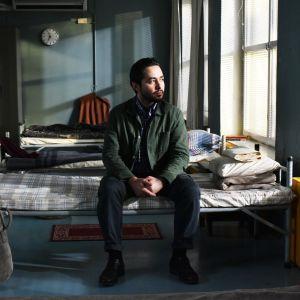 Khaled (Sherwan Haji) sitter på en säng i en flyktingscentral och ser ut genom fönstret.