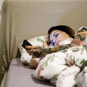 En ung kvinna ligger i sängen och tittar på sin mobiltelefon.