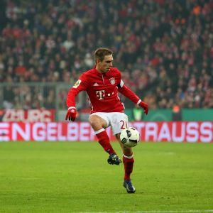 Rödklädde fotbollsspelaren Philipp Lahm håller fotbollen i luften med högerfoten.
