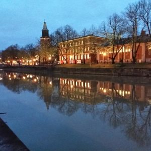 En kvällsbild över Katedralskolan och Åbo domkyrka som avspeglas i Aura å