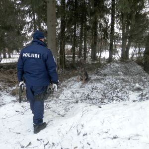 Polisen undersöker terrängen runt mordplatsen på Getbrovägen i Jakobstad med schäferhund