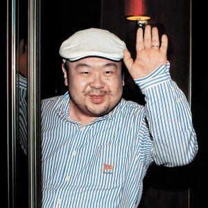 Kim Jong-nam iklädd randig skjorta och vit keps lyfter sin hand i en hälsning till kameran.
