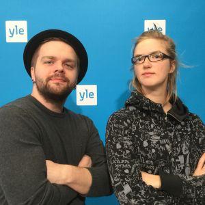 Oscarsentusiasterna Tage och Lisa står mot en blå ylevägg och poserar med armarna i kors.