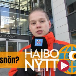 Pojke som står utanför meteorologiska institutet i Helsingfors med mikrofon i handen.