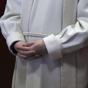 En präst som står med knäppta händer