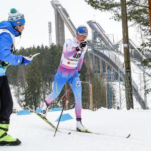 Anne Kyllönen får höra mellantider under lopp. I bakgrunden hoppbackarna i Lahtis.