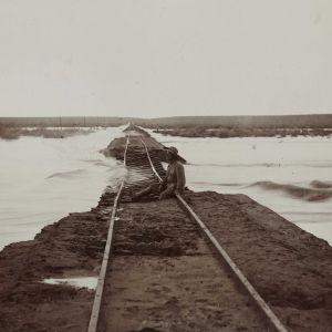 En man sitter på en översvämmad järnväg mellan Keetmanshoop och Lüderitz i dåvarande Tyska Sydvästafrika, nuvarande södra Namibia. Bilden är tagen omkring 1910.