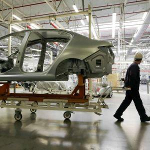 Vy inifrån en bilfabrik där en arbetare drar en vagn med en halvfärdig bil.