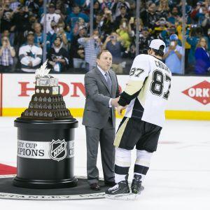 Gary Bettman skakar hand med Sidney Crosby på isen.