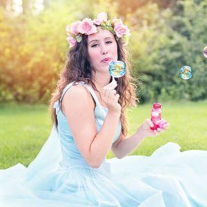 en kvinna med en blomsterkrans på huvudet sitter i gräset och blåser såppubblor