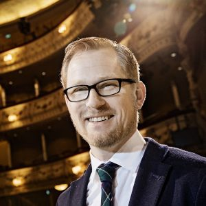Joachim Thibblin klädd i kostym i Svenska teaterns sal.