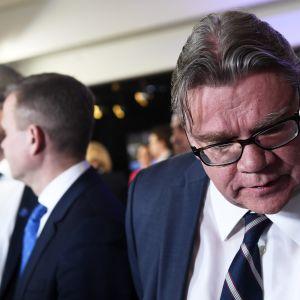 Timo Soini tittar ner i marken, i bakgrunden regeringskamraterna Juha Sipilä och Petteri Orpo.