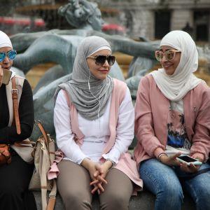 Tre kvinnor i hijab och med solglasögon sitter vid en fontän. De har mobiler i händerna