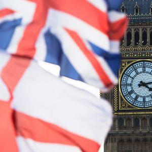 Brittiska och engelska flaggan fladdrar i vinden framför Big Bens urtavla vid brittiska parlamentet.