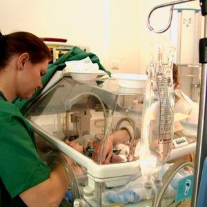 Sjukskötare vårdar prematur i kuvös.
