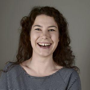 Porträtt av De Grönas riksdagsledamot Emma Kari som skrattar.
