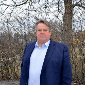 fredrik Eklundh i kavaj och skjortaframför buskar, bakom skymtar bostadshus.