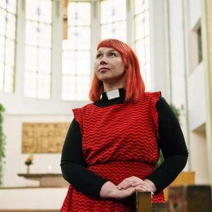Pastor Marjaana Toiviainen i röd klänning. Bilden är tagen lätt underifrån och Marjaana har blicken vänd uppåt.