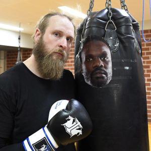 Robert Helenius bredvid en boxningssäck med Chisoras ansikte.