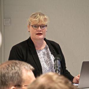 Katrin Sjögren står och pratar vid en dator