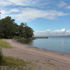 Lång sandstrand med utsikt mot Helsingfors.