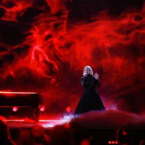 Kvinna i svart klänning och man vid flygel