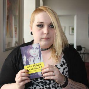 Ung kvinna håller upp bok.