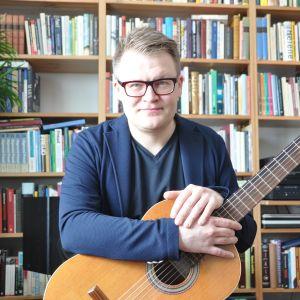 Forskaren Juha Torvinen sitter i sitt vardagsrum med gitarren i knät