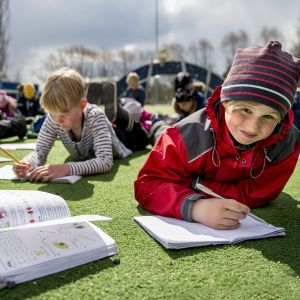 Elever i S:t Karins svenskspråkiga skola ligger på en gräsmatta och skriver i häften.