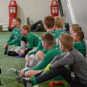 Pojkar klädda i grönvita kläder på konstgräshall  tillsammans med en man klädd i svarta idrottskläder