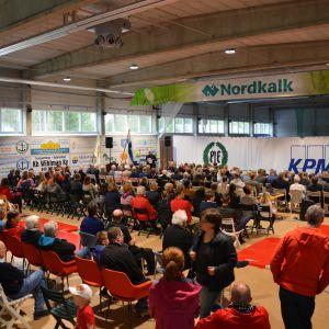 Människor sitter i en stor sal och väntar på att program inleds.