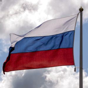 Den ryska flaggan vajar i vinden med blå himmel och några moln i bakgrunden.