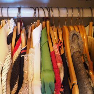 Vaatteita riippuu henkareista vaaterekissä.